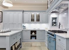 This stunning light blue kitchen features state of the art appliances. Both the cabinetry and beautiful island are painted in our very own Iris. Light Blue Kitchens, Grey Kitchens, Bespoke Kitchens, Kitchen Dresser, Kitchen Paint, Black And Grey Kitchen, Tom Howley Kitchens, Luxury Lighting, Grey Paint