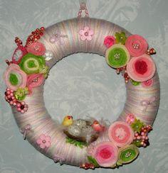 Ghirlanda realizzata rivestendo con filo di lana + fiori di feltro un anello di polistirolo.