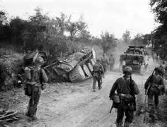 US infantry & a M5 Scout vehicle passed a knocked out German Panther tank...