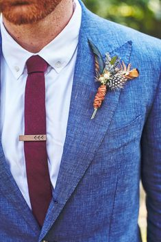 Personal Details: Skip the predictable and add your own touch. This boutonniere is unique with its leather-wrapped stem and dotted feather, but you can opt for any elements found in the rest of your decor. (via Stephanie Sorenson / The Knot)
