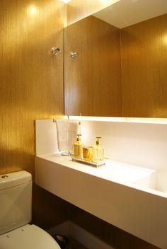 Neste lavabo, foi usado diversos recursos para trazer requinte, a começar pelo nanoglass branco escolhido para compor bancada. O restante da parede ganhou papel no tom dourado. Acima da bancada, foi usado um espelho iluminado para aumentar o ambiente.