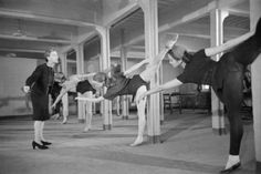 Marie Rambert, founder and director of the Ballet Rambert (left), directs members of her company as they rehearse in the games room of the factory hostel. The rehearsal is taking place in the morning, whilst the factory workers are busy at their jobs.