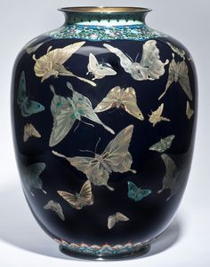 Large cloisonné enamel vase. 46.5 cm. Signed with the Hayashi lozenge seal. Circa 1900. Delicately worked in varying thicknesses of silver wire with numerous butterflies in flight against a midnight-blue ground, the shoulder scattered with chrysanthemum and paulownia, the foot with formal shield shaped overlapping panels, applied with silver rims.