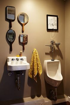 Man cave done right. Click on thru. I love the old hand mirrors, but I'm sure a man would love the urinal. Boys. ;p  There's a boy's club vibe in the half bath, which has a sink and a urinal. Four hand mirrors commonly found in barber shops are stand-ins for a traditional above-sink mirror.