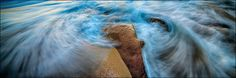 Panoramic photograph of blue swirl waves and crashing surf around a rock at the ocean shore. Image title: Circling the Stone One of my major photography themes is the subject of water. I prefer to have a longer exposure which creates a sense of movement in the water of this panorama. All photographs are original and photographed by artist Bob Estrin. Photographs are available in a variety of sizes as a print or as a gallery wrapped canvas. Panoramic photograph sizes available: Using the...