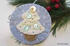 This all natural cotton batting Christmas tree is hand cut in two pieces and blanket stitched onto a nice light blue wool felt ornament and