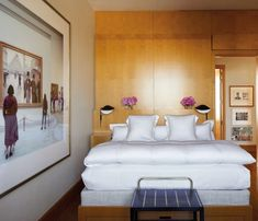 Aerin Lauder's master bedroom in Paris exudes charm, thanks to walls that are clad in sycamore. Enhancing the look are a Vintage Gio Ponti luggage rack and Serge Mouille sconces. The photograph to the left of the bed is by Thomas Struth.