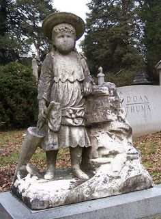 """Chunkie    Referred to by cemetery personal as """"Chunkie"""", this statue appears atop a monument at Spring Grove Cemetery in Cincinnati, Ohio. The cemetery's staff claims that it is the most frequently visited grave in the entire cemetery. Coins, flowers, and small toys are often placed at her feet as an offering."""