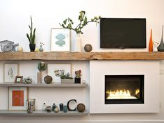 A bump-out fireplace is made to look built-in with the addition of a timber-beam mantel and a set of side shelves.  The rough-hewn timber mantel extends past the fireplace to give the room a gorgeous focal point and provide a surface to display artwork and glassware.