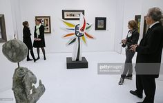 Visitors look at 'Le Tournesol' (The Sunflower), a 1952 ceramic piece by French artist Fernand Leger during the press opening of the Foire Internationale d'Art Contemporain (FIAC, International Contemporary Art Fair) at the Grand Palais on October 22, 2014 in Paris.
