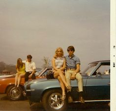 Double date, sitting on the cars. Vintage photo of two couples from May 1970.