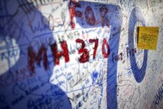 A card with a drawing of an airplane is pinned on a dedication board with well wishes and messages for people involved with the missing Malaysia Airlines flight MH370 - Kuala Lumpur International Airport.