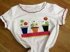 Camiseta con aplicaciones de fieltro, flores de ganchillo y cinta decorada.
