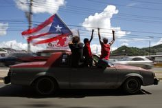People ride atop a vehicle waving a Puerto Rican flag during elections in San Juan, Puerto Rico, Tuesday, Nov. 6, 2012. Puerto Ricans are electing a governor as the U.S. island territory does not get a vote in the U.S. presidential election. But they are also casting ballots in a referendum that asks voters if they want to change the relationship to the United States. A second question gives voters three alternatives: become the 51st U.S. state, independence, or sovereign free association, a…