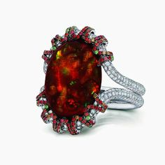 A 13.18-carat oval Mexican fire opal serves as a center stone of this ring extended by flames of green tsavorite garnets and orange-red sapphires.