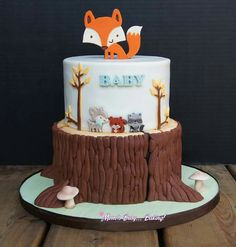 Woodland baby shower cake featuring a cute fox and wood stump.