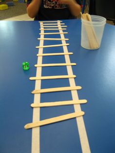 "I did this fun and easy game for unit about fire fighters and construction workers.  Place two long strips of tape up the table and give the kids dice and a cup of popsicle sticks. They roll the dice, count the dots and add the rungs to the ""ladder."""
