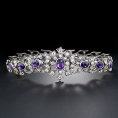 A rare, regal and astonishingly beautiful late-Victorian/early-Edwardian bracelet, circa 1890- 1900, in glorious purple and sparkling white (diamonds). This magnificent antique treasure is handcrafted in silver and 14 karat gold and is comprised of gracefully graduated diamond-set sections - plus the centerpiece - each of which is composed of a single faceted oval amethyst and an array of sparkling old mine-cut diamonds. This fabulous bauble measures 7/8 inch wide by 6 3/4 inches long