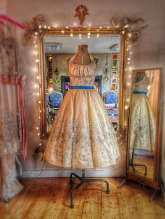 Embellished nude tulle over antique ivory silk halter neck tea length wedding dress by Joanne Fleming Design. Teal accent