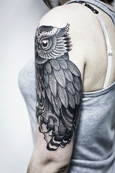 Black owl tattoo on upper arm. Beautiful linework.
