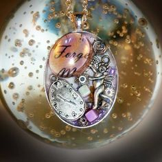 """Forgotten Time - Large silver plated pendant with glass jewels, and silver plated charms embedded into resin, on a vintage script background. Size - 3cm x 4cm. On a silver plated chain, length of 18"""" - 20"""". Angel wing at the end of the extender chain. On Folksy. Price £18.99"""