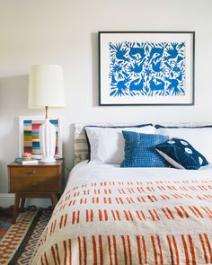 Framed blue otomi and indigo cussions and rug add a touch of bohemian that adds on to the midcentury sidetable of this bedroom