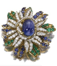 EMERALD, SAPPHIRE AND DIAMOND BROOCH, 1960S of flower head design, set at the centre with a sapphire cut en cabochon, within surrounds of brilliant-cut diamonds, circular-cut emeralds and similarly cut sapphires