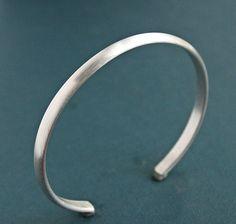 Robuste, gewölbte Draht hat in dieser Männer massiv Sterling Silber Manschette Armband geschmiedet worden. Die dünne Band hat zu einem hellen, gebürsteten satin Finish abgeschliffen worden. Ein einfaches maskulinen Design für den Alltag. Ideal zum Stapeln mit meinem Lederarmbänder, siehe letztes Foto.  Manschette sind in folgenden Größen möglich (Bitte wählen Sie aus dem Dropdown-Menü):  S/M-7,75 Zoll (19,7 cm) L/XL-8.25 Zoll (21 cm)  Messungen sind Gesamt Umfang einschließlich eine...