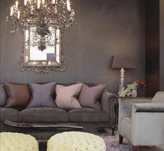 soft cozy glam: grey gray velvet sofa, silver upholstered chair, chandelier, gilded mirror, gray paint
