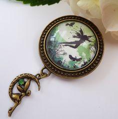 Diese romantische Brosche besteht aus antikgoldfarbenem Metall und einem handgearbeiteten Glas-Cabochon mit zauberhaftem Elfenmotiv.