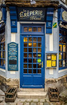 blue door, hand painted signs, and old crates | La creperie bleue restaurant in Rouen, France by Richard Depinay