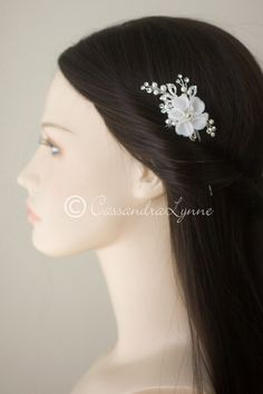 This classic bridal hair pin has a layered, five-petal flower of ivorypoly-silk accented by glass rhinestones, ivory pearl sprays and leaf shapes. The entire p