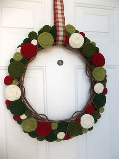 Holiday felt rosette wreath by handmadecolectibles on Etsy - looooove this use of felt. I think different shades of green would look amazing year round.