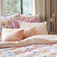 Guest room or Master bedroom.  Pillows in patterns. Orange pink and purple bedding. Love!