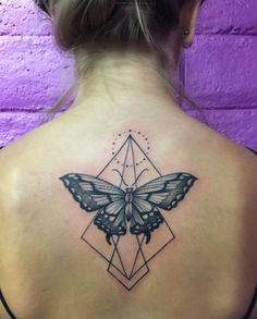 Blackwork butterfly on back with geometric accents by Marked Studios