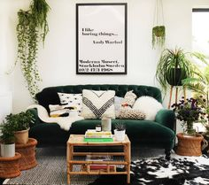 Green Velvet Sofa styled in monochrome family home by The Only Girl in the House with lots of house plants, hanging plants, string of pearls plant and ponytail palm in basket. Black and white rug and cowhide. Andy Warhol quote print, I like boring things. how to style a velvet sofa from DFS Bailey Sofa and sofaworkshop