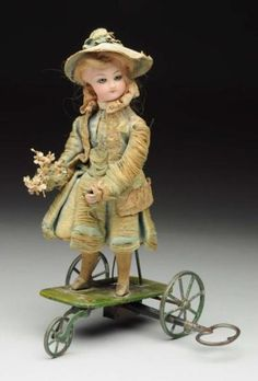 "French Mechanical Toy. François Gaultier bisque fashion head with glass eyes; key wind mechanism moves her head from side to side and arms goes up and down; original clothing. Size 9"" T."