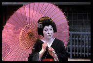 Elderly Geisha posing with pink umbrella in the Gion district of Kyoto, Japan