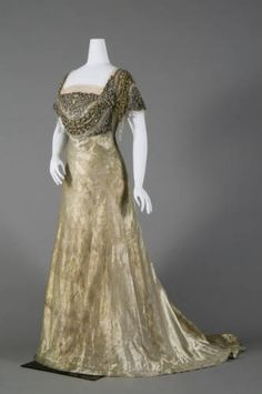 Dress, 1910. Reville & Rossiter. Dress, evening-style, of twilled silver cloth. Square neck and short sleeves. Bodice trimmed with ornaments of silver bugle beads, seed beads, and rhinestones. Draped light pink tulle at neck and sleeves. Bodice lined with white chiffon and satin; steel stays in built-in corset. Floor-length skirt with slight train. Metal weights in skirt and throughout bottom hem.