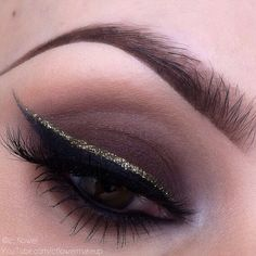 Brown smokey eye with gold and black winged eyeliner makeup. Fall look.