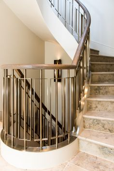 Helix staircase. Balustrades in Almond Gold PVD Stainless steel (yes, stainless steel not brass) by John Desmond Ltd.