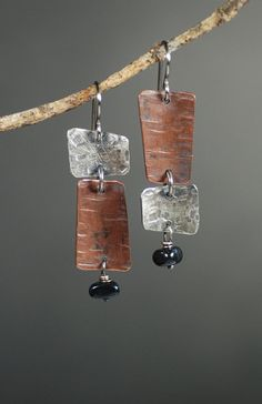 Pieces of copper and sterling silver have been textured with my own customized hammers. I have given them a gentle curved shape, and accented them with
