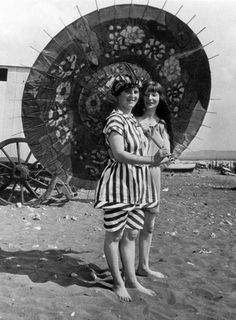 Two young Edwardian women in bathing costumes posing for the camera at the beach, c 1910.