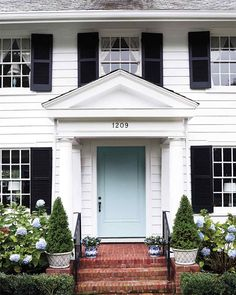A classic white painted house with black shutters is refreshed with a pale blue front door.