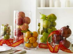 Easy and Elegant Thanksgiving Centerpieces In this fresh update of the classic cornucopia, clear glass vases overflow with apples, pears, tangerines, and both ripe and green pomegranates. Accent with ribbon curling in and around the fruit.