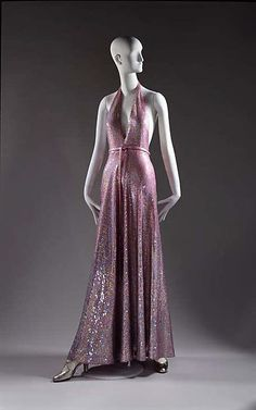 Evening dress, Halston, 1974: This dress incorporates the popular style of a halter neck line and glamorous, flashy sequined fabric into a sleek, fluid design.