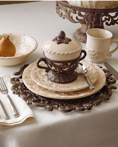 """GG Collection   20-Piece Ceramic Dinnerware Service    Scrolls and antiquing create easy elegance in this dinnerware service. All pieces are handmade and finish will vary slightly. From the GG Collection.    •Ceramic with antiqued cast-aluminum accents.  •20-piece set includes four five-piece place settings (dinner plate, salad/dessert plate, cereal bowl, mug, and saucer).  •Dinner plate, 11""""Dia. •Salad/dessert plate, 8.5""""Dia. •Cereal bowl, 8.5""""Dia. •Saucer, 7.25""""Dia. •Dishwasher safe."""