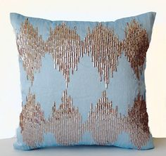 Sequin embellished blue art silk pillowcase with metallic beige ikat pattern embroidery. These unique sequins give a subdued hue but sparkle with silvery shine under strong light. Use it to add a capt