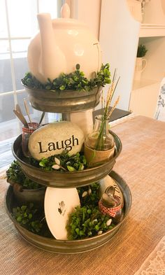 My everyday Rae Dunn inspired Farmhouse Table Centerpiece - 3 Tier Stand from Hobby Lobby, Rae Dunn Tea Pot, Stationary Paper Weight and Farm Round plates. Love & Laugh Rocks from Joann Fabrics, Fancy Spoons and Knives from Marshalls, Topiaries from Hobby Lobby.