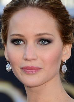Jennifer Lawrence paired a glistening charcoal smoky eye with a head-turning twisted bun updo.